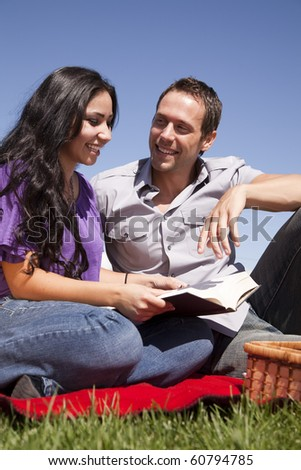 A couple is sitting on a red blanket reading a book
