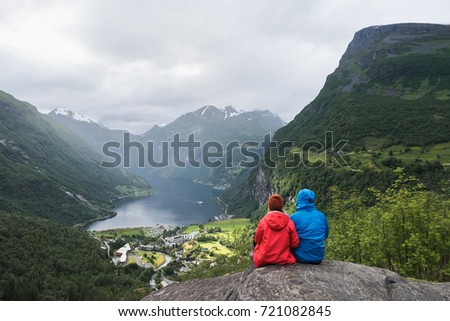 A couple is sitting on a rock with looking at the fjord and mountains. Tourist village of Geiranger and the Geirangerfjord, Norway