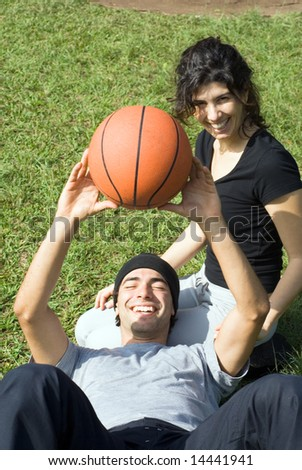 A couple is sitting on the grass in a park.  The woman is looking at the camera and the man is resting on the woman's lap.  The man is holding a basketball above his chest.  Vertically framed photo. - stock photo