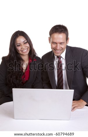 A couple is smiling and looking at a laptop. - stock photo