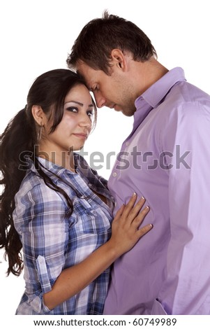 A couple is standing intimately together and she is looking. - stock photo
