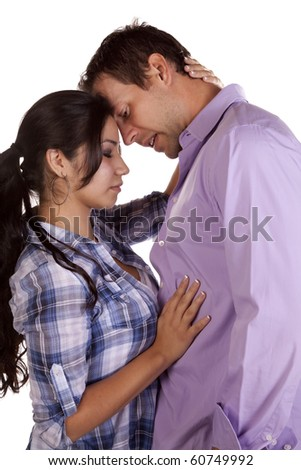 A couple is standing together with fore heads touching and very serious. - stock photo
