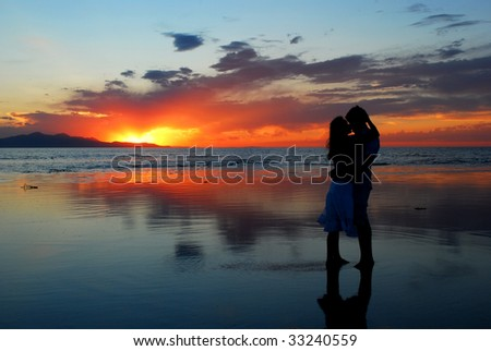A couple kissing during a sunset - stock photo