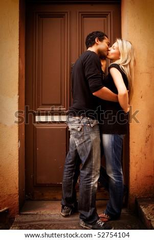 A couple kissing in an urban European setting - stock photo