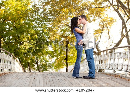 A couple kissing while walking in the park - stock photo
