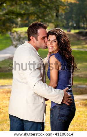 A couple kissing with the woman looking at the camera - stock photo