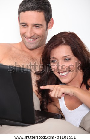 a couple laughing behind a computer - stock photo