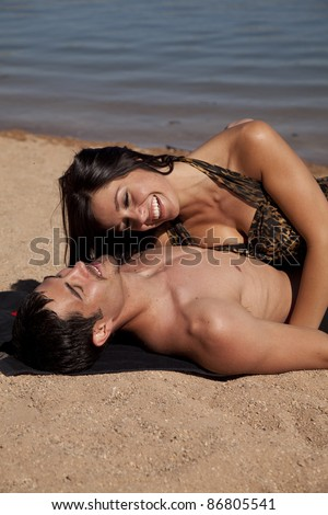 A couple laying and laughing in the sand. - stock photo