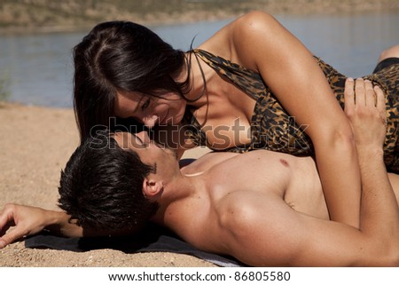 A couple laying in the sand looking into each others eyes.