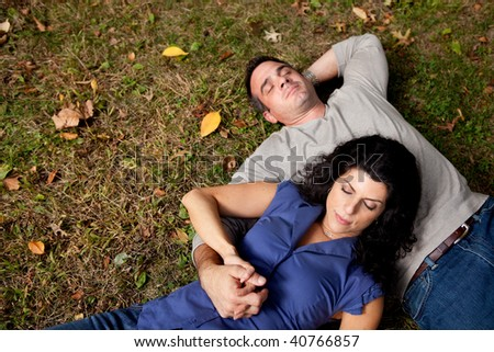 A couple laying on grass dreaming - sharp focus on female - stock photo