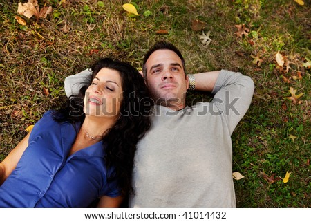 A couple laying on grass in a park daydreaming.  Focus on the woman's eyes - stock photo