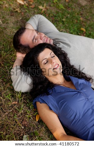 A couple laying on grass in a park daydreaming.  Focus on the womans eyes - stock photo