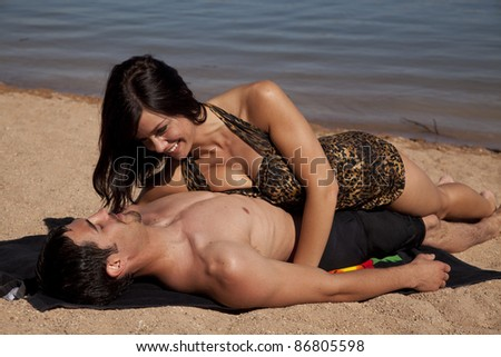 A couple laying on the beach together being close. - stock photo
