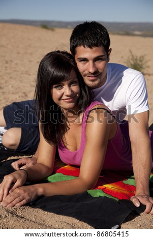 a couple laying on the sand with smiles on their faces. - stock photo