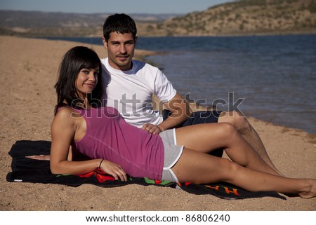 a couple laying on the sandy beach together. - stock photo