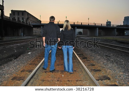 A Couple lit up by the light of a train - stock photo