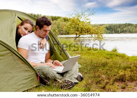 A couple looking at a computer while camping in a tent - stock photo