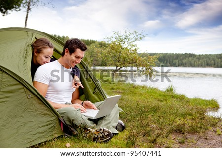 A couple looking at a computer while camping in a tent