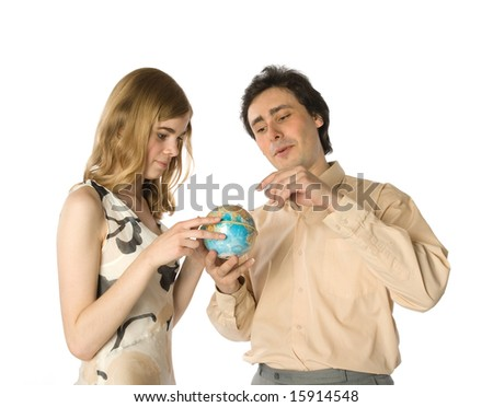 A couple looking at a small globe - stock photo