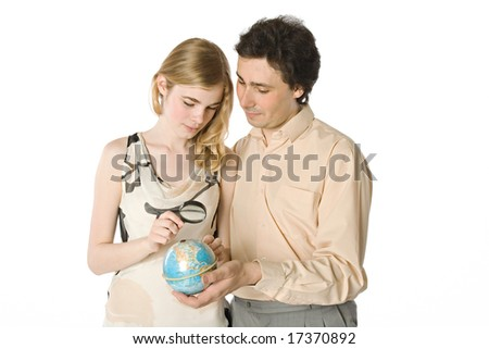 A couple looking at a small globe through a magnifier - stock photo