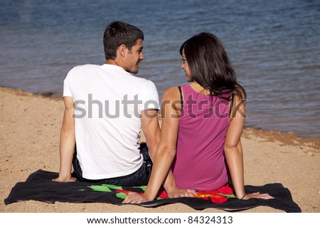 A couple looking at each other while they sit in the sand by the water. - stock photo