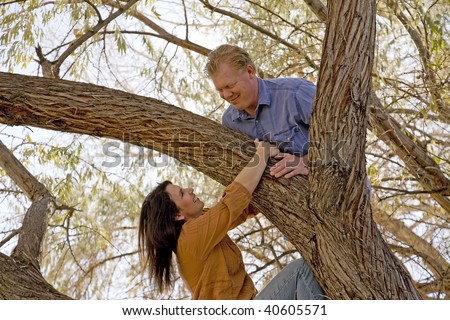 A couple looking at eachother while up in a tree. - stock photo