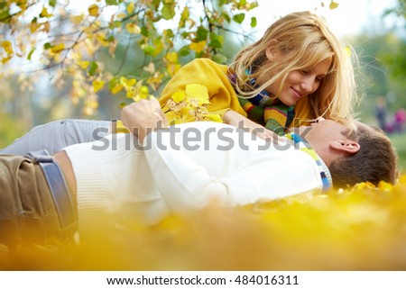 A couple lying among golden leaves and looking at each other