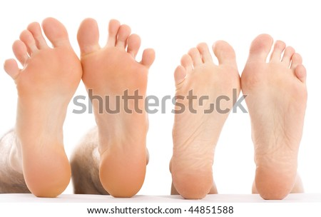 A couple lying next to eachother with naked feet. - stock photo