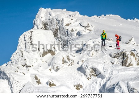 A couple of alpinists arriving to the peak after a long full-day journey. Photographed in the Pyrenees, Catalonia, Spain. The peak is 2.870 meters high. The mountaineers are 21 years old. - stock photo