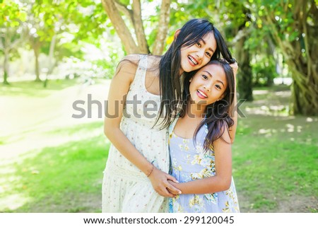 A couple of asian sisters holding hands in the forest - stock photo