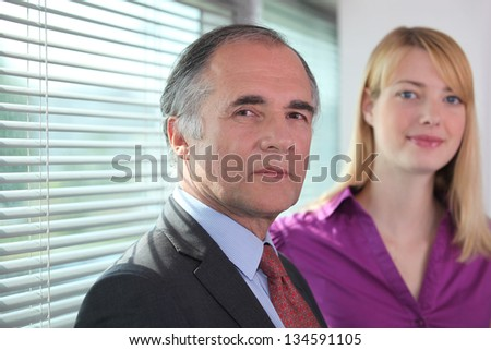 A couple of businesspeople at the office. - stock photo