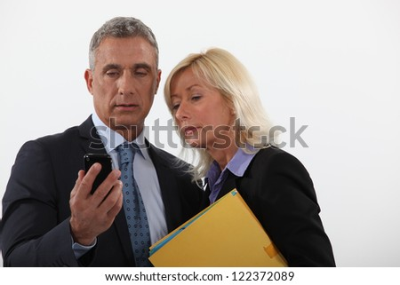 A couple of businesspeople checking their cellphone. - stock photo