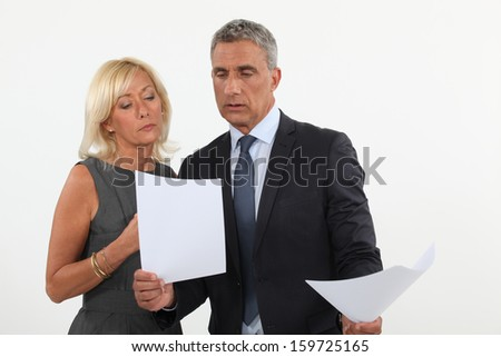 A couple of businesspeople going through papers. - stock photo