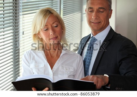 A couple of businesspeople standing by the blinds. - stock photo