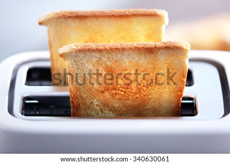 A couple of crusty toast in the toaster, close-up - stock photo
