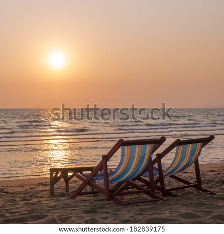 A couple of deck chairs and sunset on sea