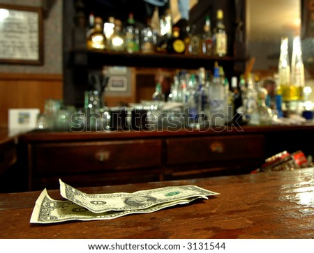 A Couple of Dollars Awaits The Bartender in a Rustic Bar - stock photo