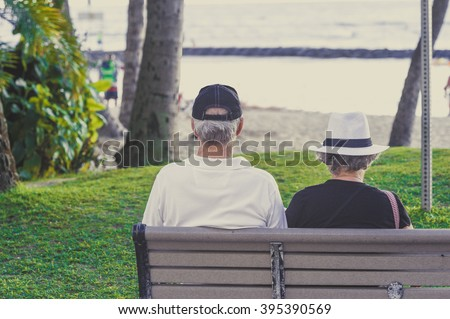 A couple of elderly people sitting on the beach - stock photo