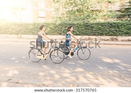 A couple of friends riding bikes on the street. Two women wearing summer clothes are riding bikes.  There are some trees on the background. selective blur with panning technique.