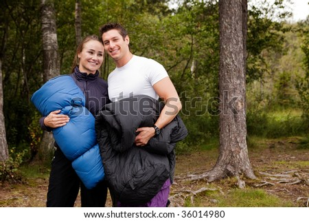 A couple of happy campers standing with sleeping bags - stock photo