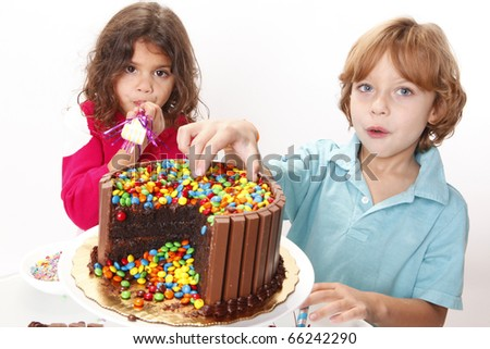A couple of kids enjoy a chocolate cake