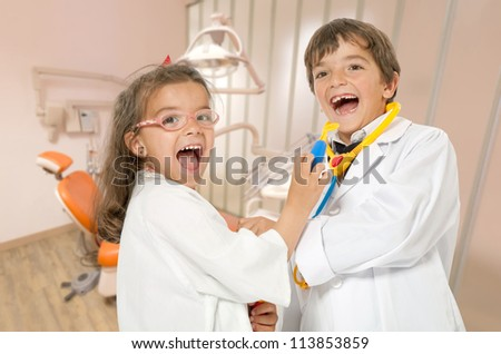 A couple of kids playing doctor at the dentist - stock photo