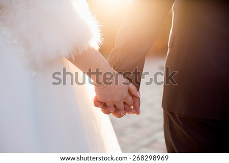 a couple of married people holding hands together shot with warm colours under sunlight - stock photo