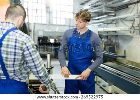 A couple of men around the milling machine at factory - stock photo