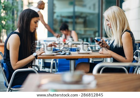 A couple of modern day female friends using technology instead of talking to each other in cafe - stock photo