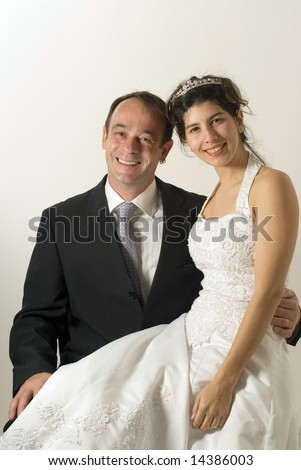 A couple of newly weds, sit on a chair, smiling for the camera. The wife sits on the husband's lap. - vertically framed - stock photo