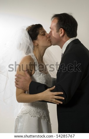 A couple of newlyweds kiss, while still in their wedding outfits. - vertically framed - stock photo