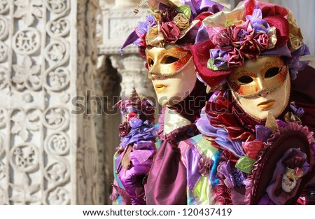 A couple of purple jokers . Marble column as background . Venice carnival 2012 - stock photo