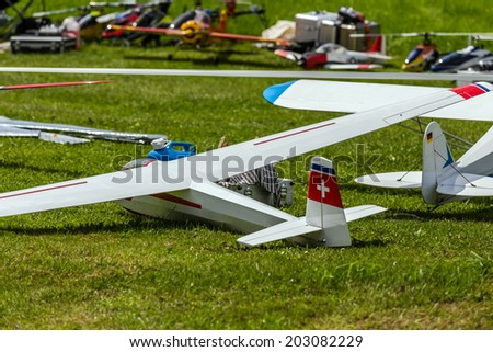 a couple of remote controlled planes lying on the meadow - stock photo