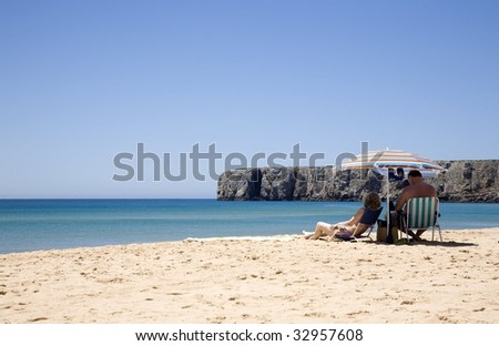 A couple of senior man and woman, sunbathing in a beach under a colourful umbrella at the Algarve, Portugal - stock photo
